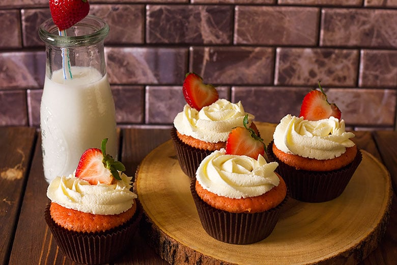Delicious strawberry cupcakes with a bottle of milk on the side.