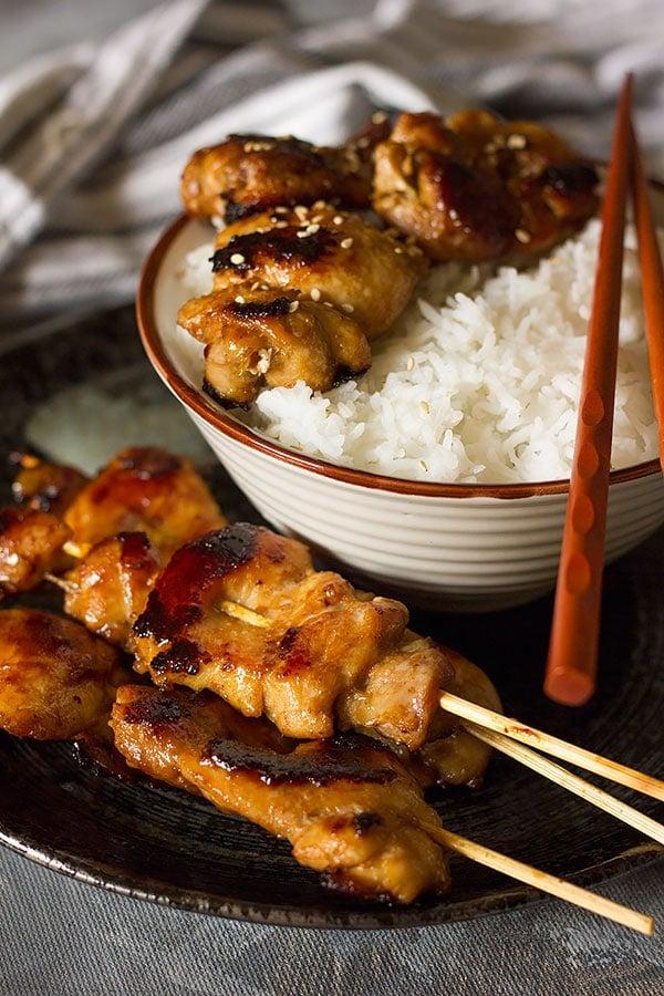 Teriyaki chicken skewers on a black plate.