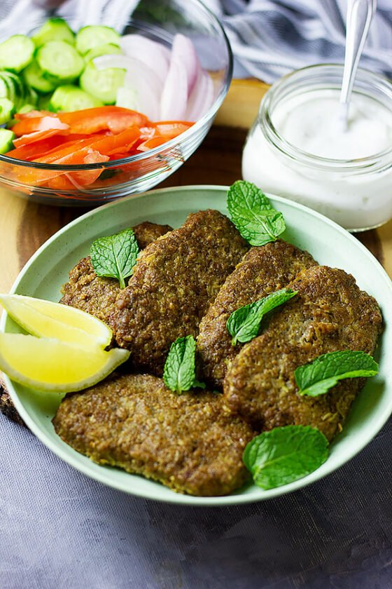 Gyros meat served on a light green plate.