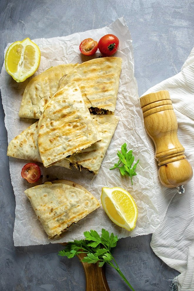 Ground beef Quesadilla slices on white parchment paper.