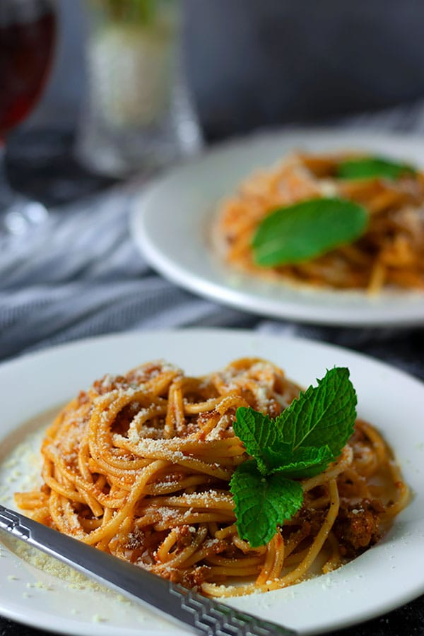 Close up image of spaghetti bolognese garnished with mint leaves.