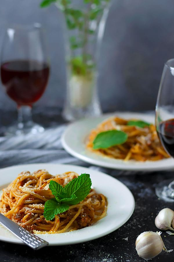 Spaghetti bolognese served in a white plate.