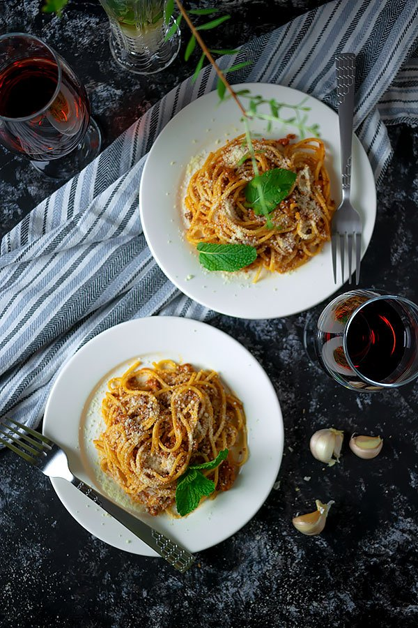 Two plates of spaghetti bolognese garnished with parmesan cheese.