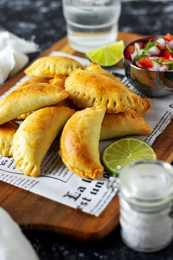 Freshly baked beef empanadas on parchment paper.